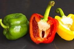 Gemüsepaprika grün und rot und gelb auf schwarzem Hintergrund Bestandteil der Nahrung Stockbilder