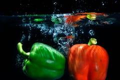 Gemüsepaprikatropfen in Wasser auf schwarzem Hintergrund. Stockbilder