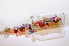 Gemstenen in een fles op een witte achtergrond stock foto