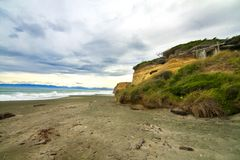 Black sand wild beach in Catlins with primitive coastal wooden beach house in the cliff rocks, wind shaped trees, Gemstone beach. Dramatic cloudy seascape of royalty free stock photo