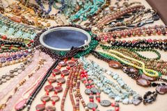 Gemstone bracelets and necklaces made of malachite, rose quartz, larimar, mahogany obsidian, unakite, amethyst, chalcedony, green. Jasper stones and crystals stock photography