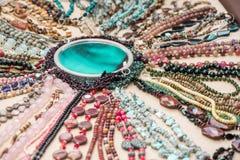 Gemstone bracelets and necklaces made of malachite, rose quartz, larimar, mahogany obsidian, unakite, amethyst, chalcedony, green. Jasper stones and crystals royalty free stock photos