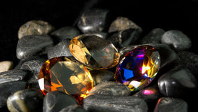 Gemstone Collection. Colorful faceted gemstone collection sitting on rocks. Black background Stock Photography