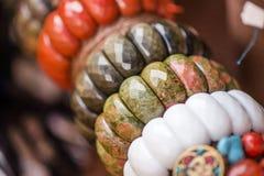 Gemstonearmband och halsband i rad Smycken som göras av den röda jaspisen, unakitestenar, obsidianstenar och den vita onyxstenen fotografering för bildbyråer