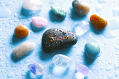 Gemstones and soul. Colorful healing stones gemstones and a stone with the word soul over bright blue background with drops of water Stock Photos