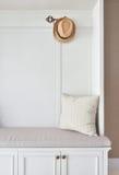 Gemütlicher Sitz mit weißem Rahmen mit gestreiftem Kissen und Panama-Hut Stockfotos