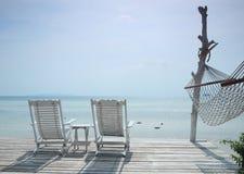 Gemütlicher weißer Strandstuhl und Hängematte, die Meerblick gegenüberstellt Lizenzfreie Stockfotos