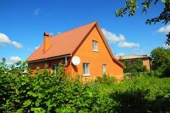 Gemütliches Backsteinhaus mit alter verblaßten roten dem Metalldachplatte und -kamin im Freien Schlechtes Deckungs-Äußeres Lizenzfreie Stockfotos