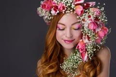 Gemustertes Rothaarigemädchen mit hellem Make-up und ein Kranz des Frühlingsflusses Stockfotos