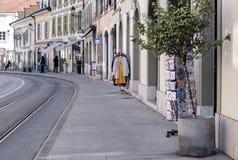 GENÈVE SCHWEIZ - FEBRUARI 28, 2019: gatan med litet shoppar och spårvagnstänger i Carouge den gamla staden, royaltyfri foto