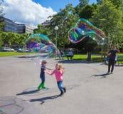 Genève, Zwitserland - Juni 17, 2016: De kinderen en met zeepbelsaantrekkelijkheid bij park Stock Fotografie