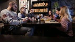GEN Z Amigos jovenes que usan los teléfonos elegantes en café almacen de metraje de vídeo