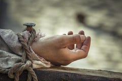 Genagelte Hand auf Kreuz Stockbild