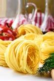 Genauer Blick auf gelben Teigwarennestern mit Tomaten auf dem Hintergrund stockbild