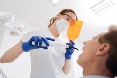 Genauer engagierter Zahnarzt, der durch spezielle Linse schaut Lizenzfreie Stockbilder