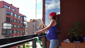 Genauer sauberer Staub der schwangeren Frau vom Balkon des Glases zu Hause stock footage