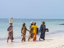 Gående fiska för lokala kvinnor på en strand i Zanzibar Arkivfoton
