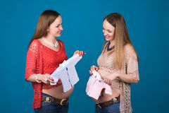 Gender of a baby. Photo of two pregnant sisters - twins - with clothes for baby Royalty Free Stock Photo
