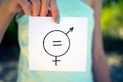 Gender definition. Concept, a piece of paper with a female and a male symbol in a woman`s hand royalty free stock images