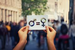 Gender equality. Concept as woman hands holding a white paper sheet with male and female symbol over a crowded city street background. Sex sign as a metaphor of stock photo