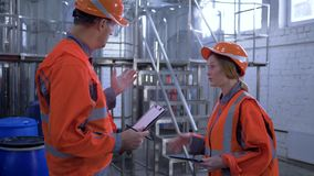 Gender equality at Factory, happy man with woman engineers in hard hats shake hands and discuss new project walk through. Plant and making calculated stock video footage