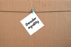 Gender equality. Note is written on a white sticker that hangs w. Ith a clothespin on a rope on a background of brown cardboard royalty free stock photography