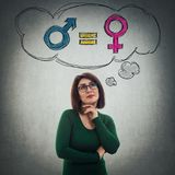 Gender equality symbol. Pensive young woman holding hands under chin wearing glasses looking up dreaming of gender equality concept with male and female symbol royalty free stock images
