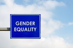 Gender Equality words displayed on blue road sign. Blue road sign displaying Gender Equality words on blue sky and white clouds background royalty free stock images