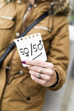 Gender parity concept. A young caucasian woman in the street shows a piece of paper with the text 50/50 written in it, with the zeros as the female and the male stock photo