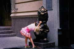 Gender question - a cat or a cat?. RnLittle girl is considering a statue.rnCity figure cat royalty free stock photos
