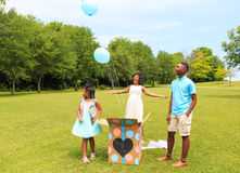 Gender Reveal Baloon Release. Beautiful African American Mother gives a room lighting smile as she reveals the gender of her child blue for boy to her daughter stock image
