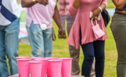 Gender Reveal Ping Pong Toss Pink. Gender Reveal party patrons participate in a ping pong toss game for the pink or girl team royalty free stock image