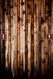 Gender Roles. Male and female gender signs on wooden panelling outside of a public restroom Stock Image