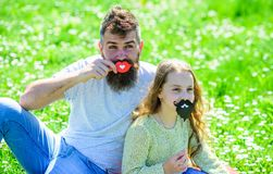 Gender roles concept. Family spend leisure outdoors. Dad and daughter sits on grassplot, grass on background. Father. Posing with lips and child posing with royalty free stock photography