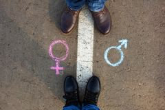 Gender symbols or signs for male and female drawn on asphalt. Male and female legs. The concept of gender equality stock photo