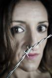 Gender violence. Scared woman behind barbed wire, a conceptual shot on gender violence stock image