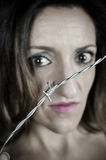 Gender violence. Scared woman behind barbed wire, a conceptual shot on gender violence royalty free stock photography