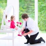 Gene a ajuda de sua filha pôr sobre uma sapata fotos de stock royalty free