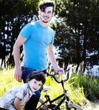 Gene a aprendizagem de seu filho montar fora na bicicleta, família feliz real na natureza enjoing da floresta do verão foto de stock royalty free