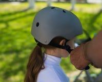 Gene a colocação sobre o capacete de segurança a sua filha fotografia de stock royalty free