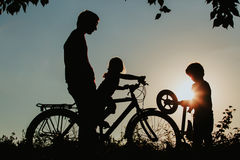 Gene com as bicicletas da equitação do filho e da filha no por do sol Fotografia de Stock Royalty Free