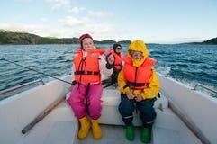 Gene com as crianças que montam o barco de motor no mar Foto de Stock