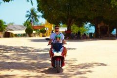 Gene com equitação do filho no 'trotinette' através da Tailândia fotografia de stock royalty free