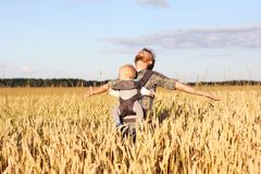 Gene com o bebê infantil no estilingue no campo da cevada Fotos de Stock