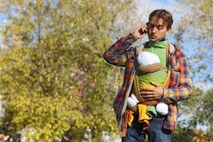 Gene com o bebê no estilingue que fala no telefone celular e que olha Imagem de Stock