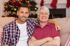 Gene com o braço em torno do avô que levanta no sofá Imagem de Stock Royalty Free