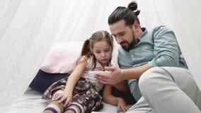 Gene com o daugher pequeno alegre que joga com smartphone e que fala em Skype pelo móbil video estoque