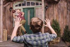 Gene com o filho pequeno que joga o futebol americano com a bola no quintal fotos de stock royalty free