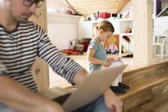 Gene com portátil e a filha pequena com tabuleta em casa Fotografia de Stock