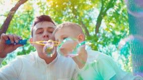 Gene com suas bolhas de sabão de sopro do filho, passatempo da família do divertimento, uma criança que tem o divertimento com se vídeos de arquivo